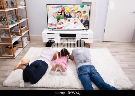 Parents With Their Daughter Lying On Carpet Watching Television At Home - Stock Image