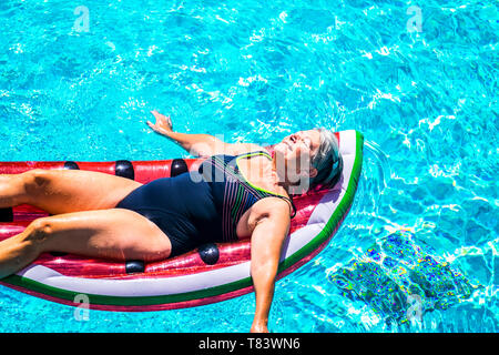 Happy beautiful aged senior lady enjoy the fresh water on a watermelon coloured lilo inflatable mattress on the blue water of swimming pool smiling an - Stock Image