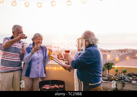 Happy senior friends having doing barbecue party on patio - Retired people having fun drinking wine and grilling meat at bbq dinner at home - Stock Image