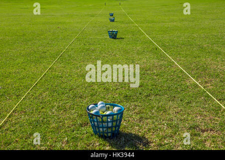 Driving range for golf practice, balls in plastic baskets - Stock Image