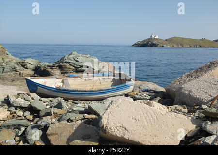 Small Boat Moored on the Rocky Shore on the Island of Kea ( Tzia ) with Lighthouse in the distance, Aegean Sea's Cyclades archipelago, Greece. - Stock Image