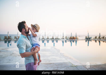 A father holding a toddler boy on beach on summer holiday. Copy space. - Stock Image
