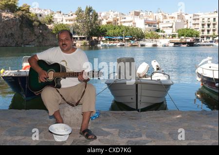 Guitar playing busker at the lake at Agios Nikolaos, Crete, Greece - Stock Image