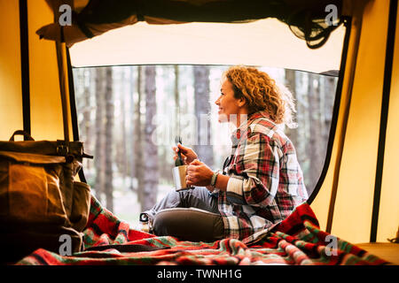 Camping with tent and adventure alternative travel vacation concept with cheerful people - beautiful adult blonde smile and enjoy the outdoors nature - Stock Image