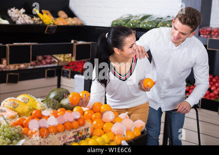 Cheerful couple examining various fruits in grocery shop - Stock Image