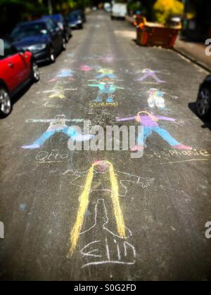 Kids taking over the street! Children's chalk graffiti drawings on a residential street - Stock Image