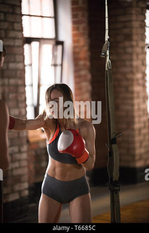 An aggressive woman boxer hitting the punching bag in the gym - Stock Image