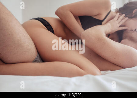 Cropped shot of passionate young couple lying on bed and having sex. Sensual man and woman making love in bedroom. - Stock Image