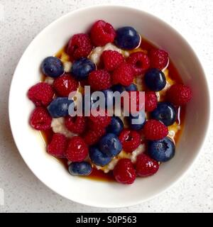 Bowl of Porridge with blueberries and raspberries and maple syrup for breakfast - Stock Image