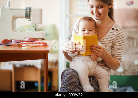 Mother and baby reading a book together at home. - Stock Image