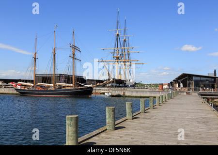Wooden boardwalk and sailing ship in harbour with Danish steam frigate Fregatten Jylland in museum. Ebeltoft Jutland Denmark - Stock Image