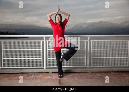 A young Asian woman does the Vrksasana Tree Pose yoga pose at Canada Place, Vancouver, British Columbia, Canada - Stock Image