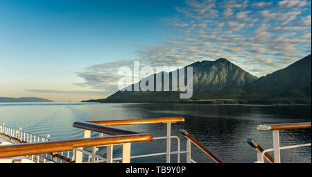 Railing and stairs, top deck of cruise ship, in golden early morning sunlight, Clarence Strait near Ketchikan, Alaska. - Stock Image