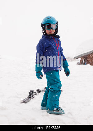 small boy in ski clothes, helmet and goggles, ready to go skiing with falling snow. - Stock Image