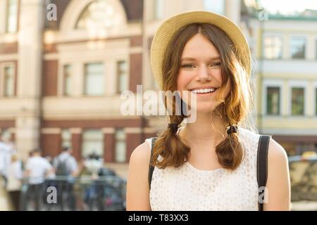 Summer outdoor portrait of smiling beautiful teenager girl 13, 14 years old wearing hat on city street, copy space. - Stock Image