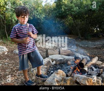 boy having marshmallow at the campfire - Stock Image