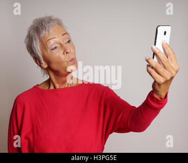 mature woman taking a smartphone selfie with duck face - Stock Image