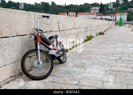 Old, stripped-down Tomos moped leaning against stone wall. Racisce, Croatia - Stock Image