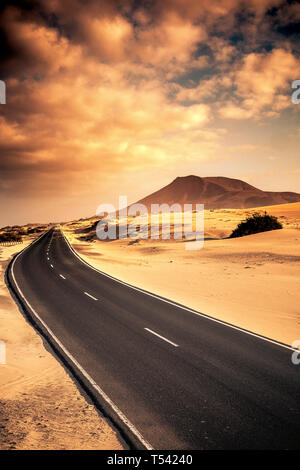 Beautiful black long road for travel conpcept with sand desert dunes on the sides and mountin in the beakcgorund - sunset warm cloudy sky - scenic lan - Stock Image