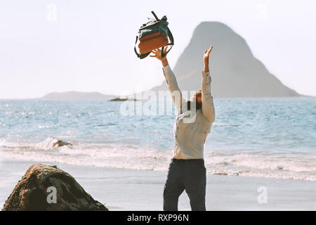 Happy man throws up backpack on sea beach travel active summer vacations outdoor lifestyle adventure trip euphoria emotions - Stock Image