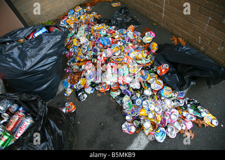 Pile of crushed soda cans and garbage bags in an alleyway - Stock Image
