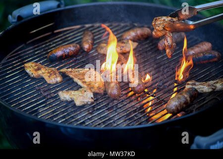 Flame grilling meat on a barbecue - Stock Image