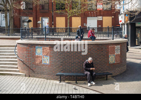 People sit in benches in George Street , Luton, UK - Stock Image