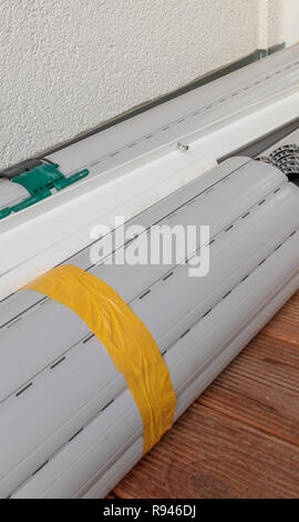 Rolled up metal shutters ready for window installation - Stock Image