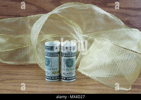 Profit and success are reflected with dollar currency placed in swirls of golden ribbon on wood grain background - Stock Image