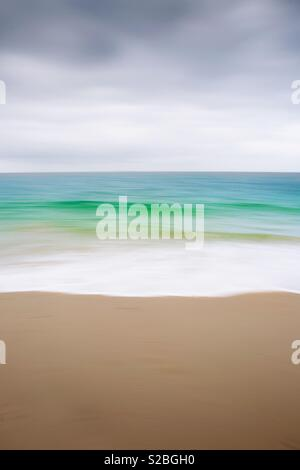 An abstract nature background of a sandy beach with white surf from an emerald green ocean under a cloudy sky with a blurred motion effect - Stock Image