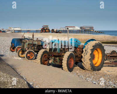 Fishermen's tractors on the beach at sunny Cromer in Norfolk. - Stock Image