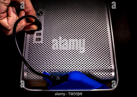 A man's hand plugging in a bright blue external hard drive storage device into a USB port on the front of an Apple Mac Pro desktop computer. - Stock Image