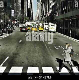 New York City street scene with girl on the phone crossing the road, NY, USA. - Stock Image