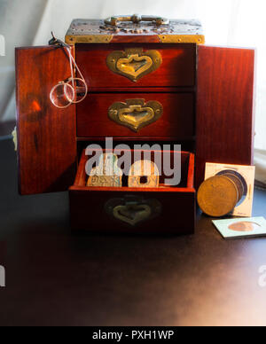 Oriental Wooden Chest houses a small treasure of ancient Japanese & Chinese Coins in Bronze and the textures of aging metals - Stock Image