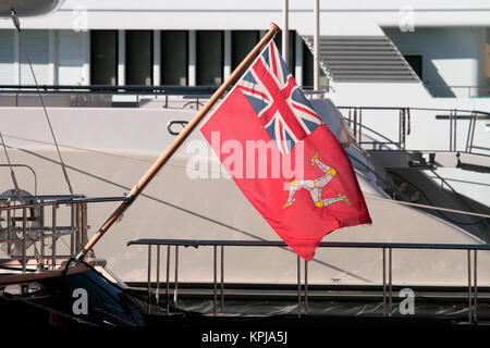 The ensign (nautical flag) of the Isle of Man on the stern of a large yacht - Stock Image