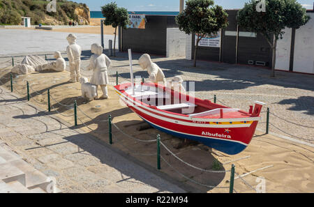 A Display Of Sand Sculpture Figures And A traditional Fishing Boat In Albufeira Old Town At Fishermans Beach, Praia dos Pescadores - Stock Image