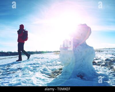 Man walk at icy snowman melting on last snowy place on spring hill. Sunny spring day - Stock Image