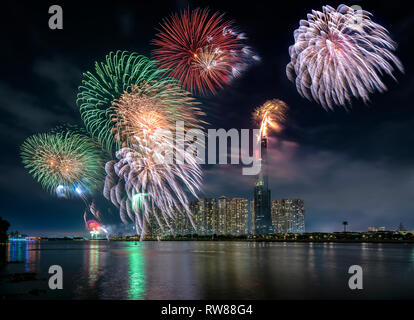Colorful fireworks in the sky glowing at night beside the skyscraper in the riverside urban area welcoming the lunar new year 2019 - Stock Image