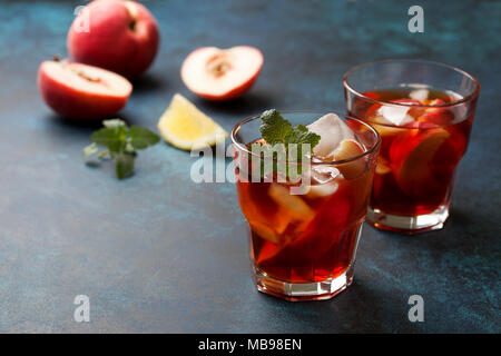 cold tea peach with ice in glasses on a blue background - Stock Image