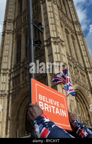 A Brexiteer protestor holds a Believe in Britain placard beneath parliament during a protest on College Greeen in Westminster, the morning after another of Prime Minister Theresa May's Brexit deal votes failed again in Parliament, on 13th March 2019, in London, England. - Stock Image
