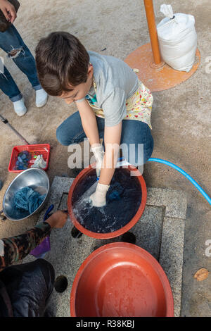 A boy uses a hosepipe to rinse cloth in a bowl as part of the process of tie dying at Namsagol Hanok Village in Seoul, South Korea. - Stock Image