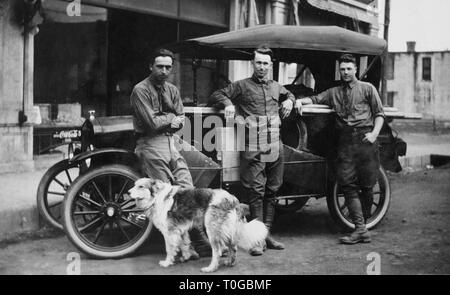 Three young men and their dog are ready for a road trip, ca 1926. - Stock Image
