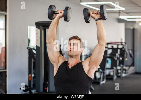Closeup portrait of young adult man muscular built handsome athlete working out in a gym, sitting and holding two dumbbell with raised arms, swinging - Stock Image
