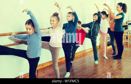 Young positive  efficient ballet dancers exercising in ballroom - Stock Image