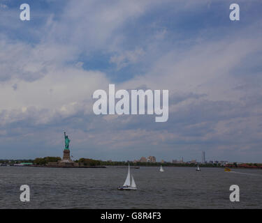 Little boats go by the statue of Liberty in New York - Stock Image