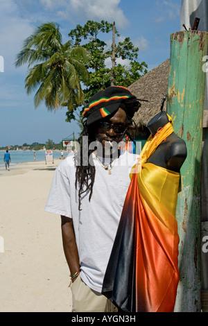 Jamaica Negril beach cool Rastafari man in front of fashion shop - Stock Image
