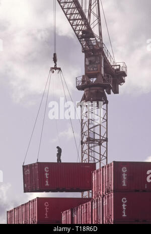 Archive of two men workers high up on top of mid air shipping container being lifted by crane off stack & lowered to ground in depot London England UK - Stock Image