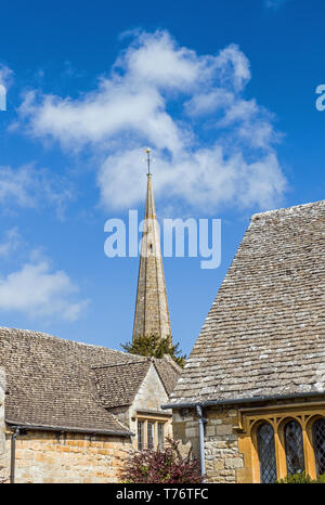 The spire of Stanton church rising between two buildings in the Cotswolds Gloucestershire England - Stock Image