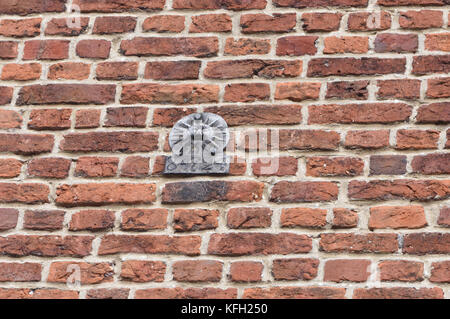 A lead fire mark for the Sun Fire Office with a policy number stamped on it nailed to a brick wall. Winchester, - Stock Image