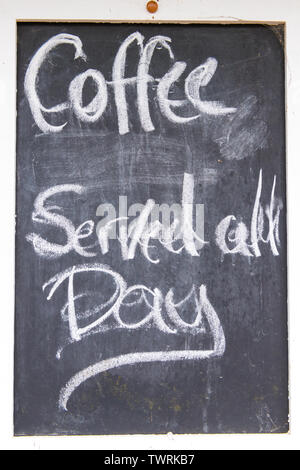 Coffee served all day sign written with chalk on blackboard - Stock Image